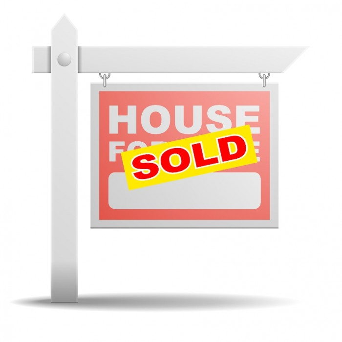 A House for Sale sign with a sticker that says Sold on top